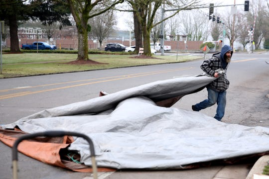 Dustin Mallory, 44, clears out his tarp from a homeless camp as a camping ban is enforced in downtown Salem on Dec. 18, 2019.