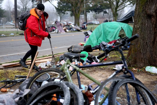 Judith Toutges, 31, rakes up trash and debris as she and others begin clearing a homeless camp as a camping ban is enforced in downtown Salem on Dec. 18, 2019.