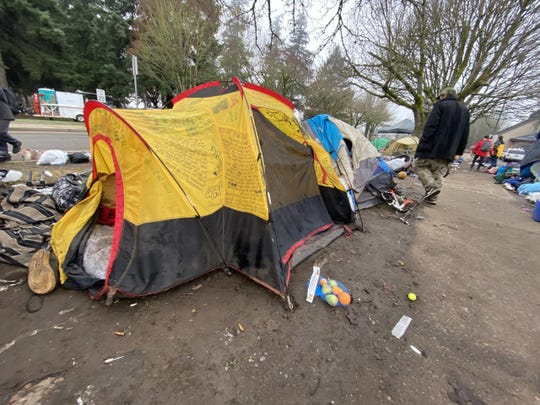 Members of a homeless camp in downtown Salem begin to dismantle their tents Wednesday morning as city officials enforce a ban on camping on city property.