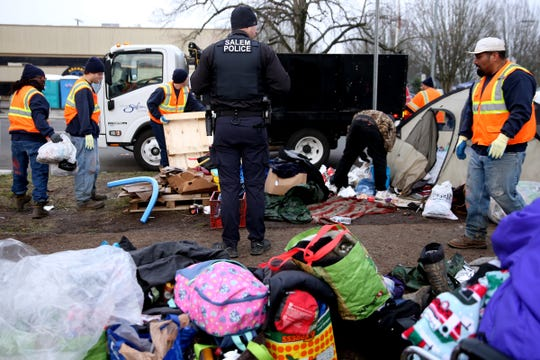 Police and an inmate work crew aide in clearing a homeless camp as a camping ban is enforced in downtown Salem on Dec. 18, 2019.