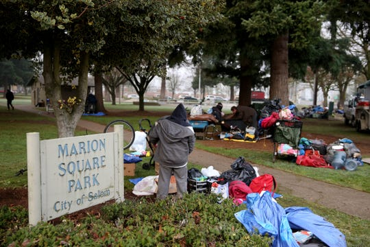 People start to bring their belongings into Marion Square Park from a homeless camp as a camping ban is enforced in downtown Salem on Dec. 18, 2019.
