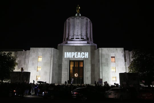 A projector is used as about 300 people rally as part of a nationwide 'Nobody is Above the Law' action outside the Oregon State Capitol in Salem on Dec. 17, 2019. The U.S. House of Representatives is set to vote on the articles of impeachment for President Donald Trump on Wednesday.
