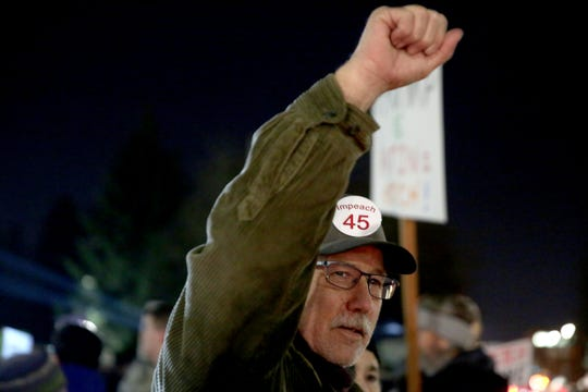 Bill Hinshaw, of Salem, cheers as passing cars honk as about 300 people rally as part of a nationwide 'Nobody is Above the Law' action outside the Oregon State Capitol in Salem on Dec. 17, 2019. The U.S. House of Representatives is set to vote on the articles of impeachment for President Donald Trump on Wednesday.