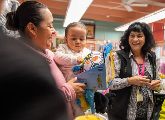 A mother smiles as she holds her baby inside the Salinas School District Family Resource Center located in Sherwood Elementary School on Dec. 17, 2019.