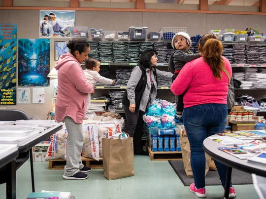 Two mothers hold their babies as they receive food and clothes from the Salinas School District Family Resource Center  located in Sherwood Elementary School on Dec. 17, 2019.