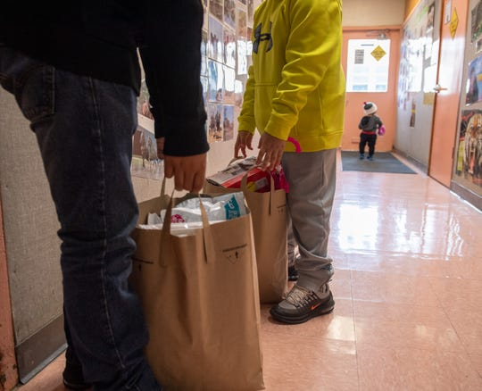 Two young boys each carry a paper bag full of toys, food and school supplies. This aid was given to them by the Salinas School District Family Resource Center located in Sherwood Elementary School on Dec. 17, 2019.