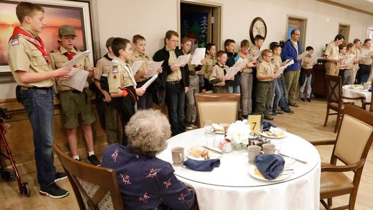 In this Thursday, Dec. 12, 2019, photo, a Boy Scouts troop, from Kaysville, sings Christmas carols to some older people in their neighborhood, in Kaysville, Utah. After almost a century of partnership, the Church of Jesus Christ of Latter Day Saints will break with the Boy Scouts of America on Jan. 1, when the church plans to pull out more than 400,000 youths and move them into a new global program of its own.
