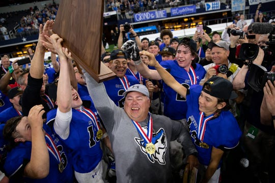 Richland Springs players with head coach Jerry Burkhart celebrate defeating Motley County 62-16 to win the state championship title at AT&T Stadium in Arlington  on Wednesday, Dec. 18, 2019.