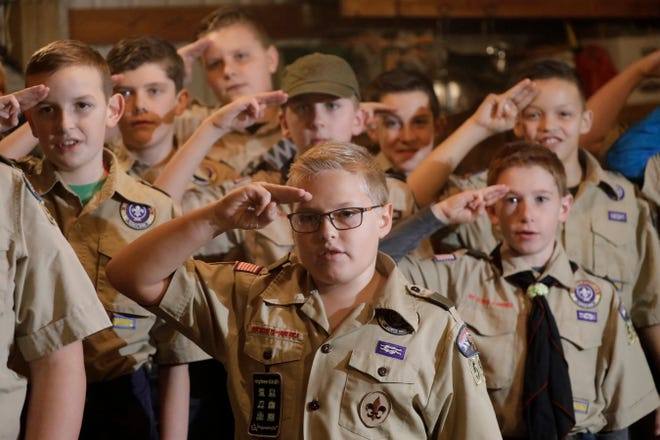 In this Thursday, Dec. 12, 2019 photo, a Boy Scouts troop salutes during their meeting, in Kaysville, Utah. For decades, The Church of Jesus Christ of Latter-day Saints was one of Boy Scouts of America's greatest allies and the largest sponsor of troops. But on Jan. 1, the Utah-based faith will deliver the latest body blow to the struggling BSA when it implements its plan to pull out more than 400,000 youths and move them into a new global program of its own. This Latter-day Saint-based Boy Scouts troop in Kaysville, though, formed outside the church structure and plans to stick with the Boy Scouts after the church ends its longtime alliance at the end of 2019.