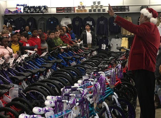 Caddo Parish District Attorney James E. Stewart Sr. talks to Caddo Parish elementary students about to receive new bicycles for Christmas at a give-away at Academy Sports Wednesday, December 18, 2019.