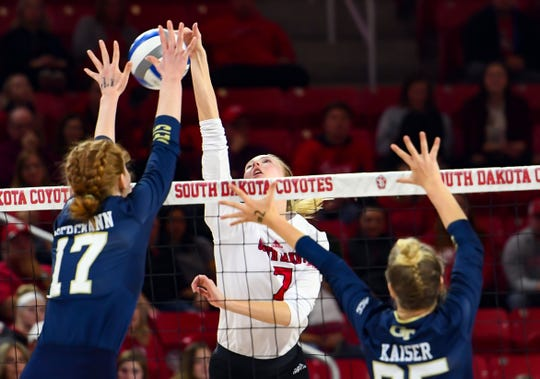 Madison Harms of USD hits the ball while Julia Bergmann and Kayla Kaiser of Georgia Tech block in the National Invitational Volleyball Championship game on Tuesday, Dec. 17, at the Sanford Coyote Sports Center in Vermillion.