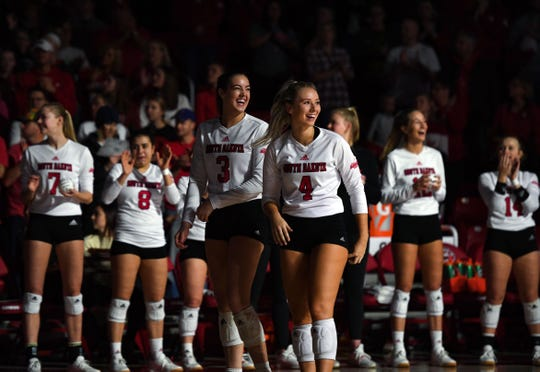 Sami Slaughter and Madison Jurgens of USD smile at the crowd as they are announced in the starting lineup before the National Invitational Volleyball Championship game on Tuesday, Dec. 17, at the Sanford Coyote Sports Center in Vermillion.