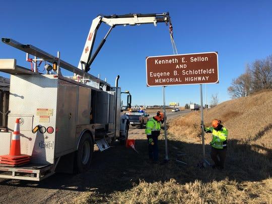 Crews set up a sign marking the Kenneth E. Sellon and Eugene B. Schlotfeldt Memorial Highway between Sauk Centre and Alexandria on Friday, Nov. 22, 2019.