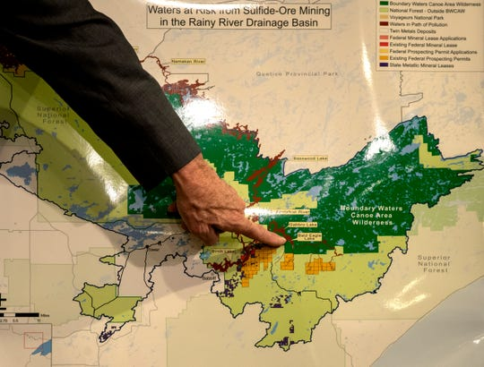 In this Dec. 17, 2019, photo former former DNR Commissioner Tom Landwehr points out runoff areas on a map of the Boundary Waters during a press conference at the Minnesota State Capitol in St. Paul, Minn. Twin Metals Minnesota has formally submitted a plan to regulators for an underground copper-nickel mine in northeastern Minnesota. (Carlos Gonzalez/Star Tribune via AP)