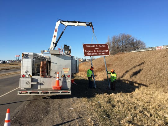 Crews set up a sign marking the Kenneth E. Sellon and Eugene B. Schlotfeldt Memorial Highway between Sauk Centre and Alexandria on Friday, Nov. 22, 2019. Sellon and Schlotfeldt worked on the highway and died in a crash along it in 1968.