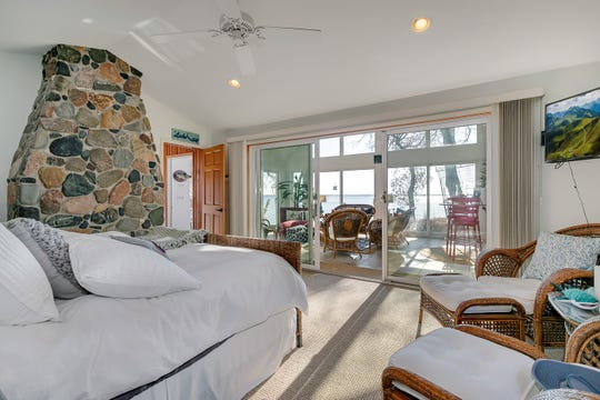 The master suite is vaulted, opens to the sunroom and features the backside of the stone fireplace.