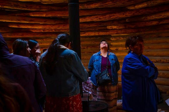 In this Oct. 24, 2019, photo, provided by Cronkite News, Pam Malone of Flagstaff, Arizona, looks up at smoke billowing from a hogan at an indigenous doula training on the Navajo reservation, in Window Rock, Ariz. Her mother kept up traditional practices in the family, but when she died, Malone stepped up to help her sister during labor. (Delia Johnson/Cronkite News via AP)