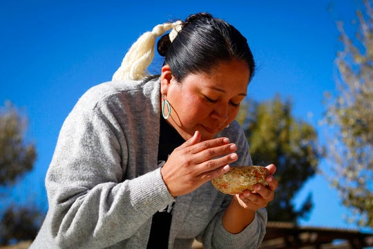 In this Oct. 24, 2019, photo, provided by Cronkite News, Nicolle Gonzales performs a smudging ceremony at doula training in Window Rock, Arizona. Smudging is the process of cleansing the body by burning herbs and plants in a shell and fanning the smoke around a person as a smoke bath. Gonzales is a nurse midwife and the founder and executive director of Changing Woman Initiative in Santa Fe, New Mexico. (Delia Johnson/Cronkite News via AP)