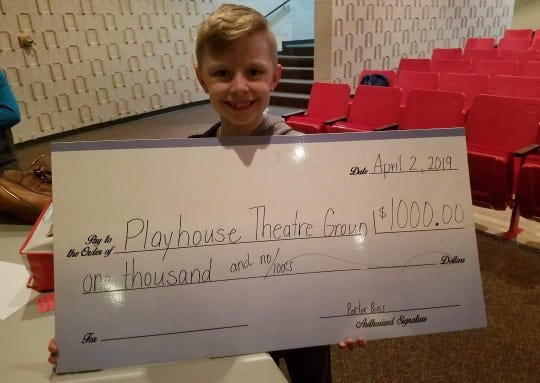 Porter Boris with a donation check to The Playhouse Theatre Group