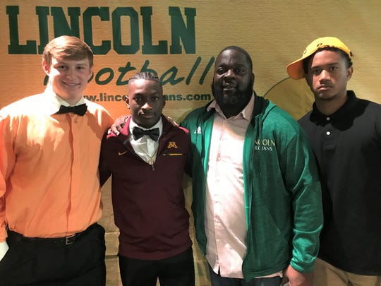 Lincoln Trojans Sage Ennis (left), Jalen Glaze, head coach Quinn Gray and Michael Pleas, Jr. gather in celebration of early signing day. Ennis is headed to Clemson, Glaze signed with Minnesota and Pleas will attend Southern Miss.