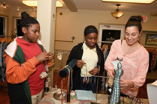 St. Lucie County Boys & Girls Clubs members Bryanna G. and Amaya E., with Melanie Wiles, seek out the perfect accessories at Whimsy Boutique in Fort Pierce.