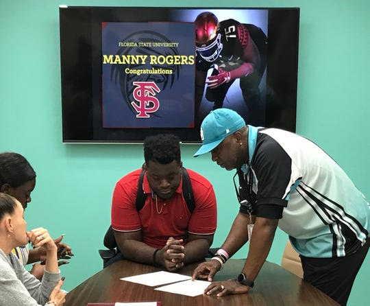 Jensen Beach football coach Tim Caffey reviews Manny Rogers' National Letter of Intent on Wednesday morning. Rogers, the No. 2 rated player on the TCPalm Super 11, signed with Florida State.