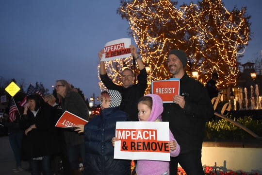 Evelyn Lizee, 8, of West Hills, (front right) demonstrates with her brother, Vaughn Lizee, and her father, Ted Lizee, back right, at a Conejo Valley impeachment event Tuesday.