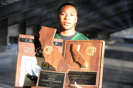 Pacifica High senior Malik Sherrod poses with the CIF-Southern Section, Southern Regional and state championship trophies won by the Tritons in a season to remember for the school from Oxnard.