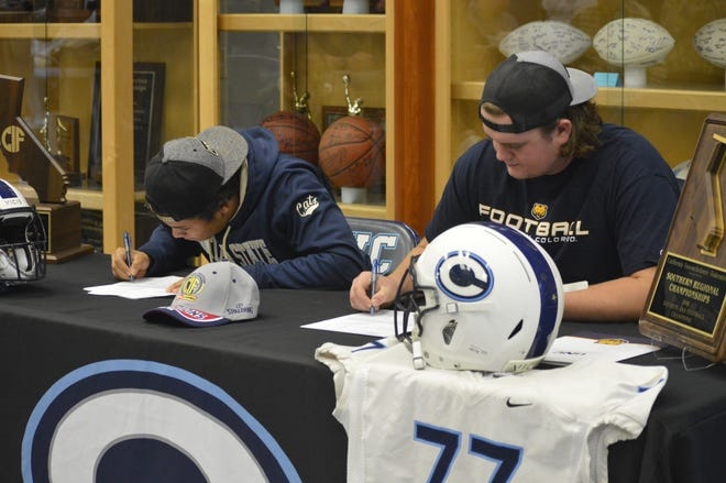 Central Valley Christian High football players Jaalen Rening, left, and Karson Oliver sign their letter of intents on Wednesday to play college football.