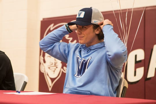 Caravel Academy's Ethan Potter puts on a Villanova hat after signing his letter of intent to the school to play football next year during a signing day ceremony Wednesday at Caravel Academy.