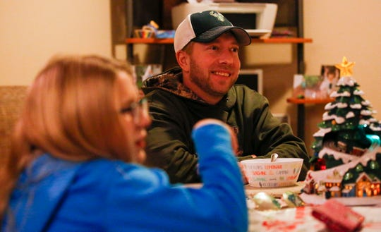 Brian Ortner laughs during dinner with his family on Wednesday, December 11, 2019, at their home in Wisconsin Rapids, Wis. Ortner was paralyzed after being hit by a tree while clearing power lines after severe storms in July 2019 and is adjusting to a new way of life.