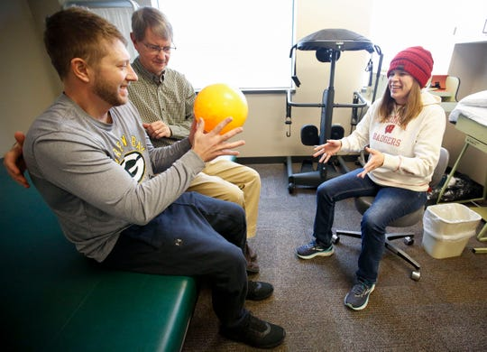 Brian Ortner catches a ball tossed by his wife, Amy Olson Ortner, during a physical therapy session with Jim Bjork, P.T., on Monday, December 16, 2019, at Aspirus Outpatient Therapy Services in Wausau, Wis. Ortner was paralyzed from the waist down after suffering a spinal injury when he was hit by a tree while clearing power lines of debris following severe storms in July 2019.