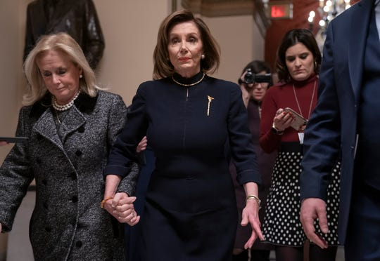 Speaker of the House Nancy Pelosi, D-CA, holds hands with Rep. Debbie Dingell, D-MI, on Dec. 18, 2019, as they walk to the chamber where the Democratic-controlled House debated impeachment charges against President Donald Trump.