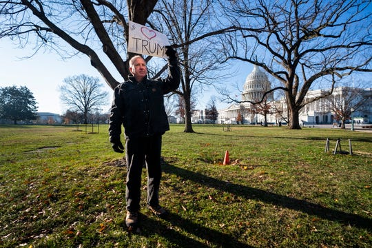A lone Trump supporter, Mark Kampf, stands opposite an 'Impeach and Remove' rally to show support for US President Donald Trump, outside the Capitol in Washington, DC, Dec. 18, 2019.