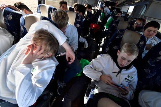 Colton Spalding (left) tries to sleep as Benjamin White plays a game and other Pied Piper teammates pass the time on the ride to Arlington Wednesday.