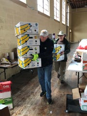 Bill Bass, front, a volunteer with MANNA FoodBank, and Rick Davis, a volunteer and board member with the Stecoah Valley Center, haul empty boxes back to the truck after a food distribution. A retired home builder, Bass has been volunteering at MANNA for four years. Davis, a former superintendent for Graham County Schools, was a lifelong educator.