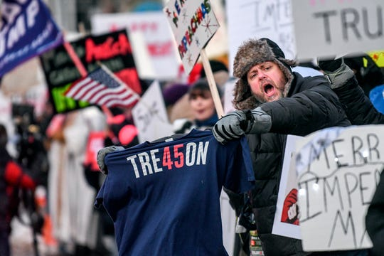 Aaron Hutchinson, of Coloma, protests against Trump with a group at the Sojourner Truth Monument on Wednesday, Dec. 18, 2019, in Battle Creek. President Donald Trump hosted a Merry Christmas rally at the Kellogg Arena.