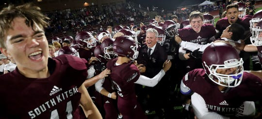 South Kitsap football coach Dan Ericson celebrates with his players after the team's 31-14 win over Rogers in September. The win snapped a 21-game losing streak for the team.