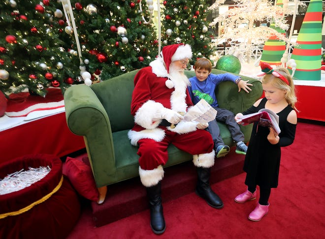 Santa Claus looks over eight-year-old Benson Trinklein's Christmas list as Benson's sister Evalyn, 6, flips through her diary to find her list to show Santa at the Kitsap Mall in this Dec. 18 file photo.