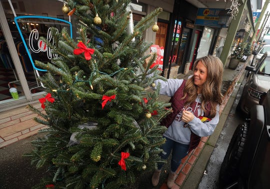 Kim Shaw restocks the South Kitsap Football team tree with snacks, rain ponchos, socks, hats and gloves in downtown Port Orchard on Thursday.