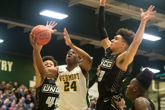 Vermont's Ben Shungu (24) leaps between UNCG's Angelo Allegri (13) and Kaleb Hunter (44) for a layup during the men's basketball game between the UNC Greensboro Spartans and the Vermont Catamounts at Patrick Gym on Wednesday night December 18, 2019 in Burlington, Vermont.