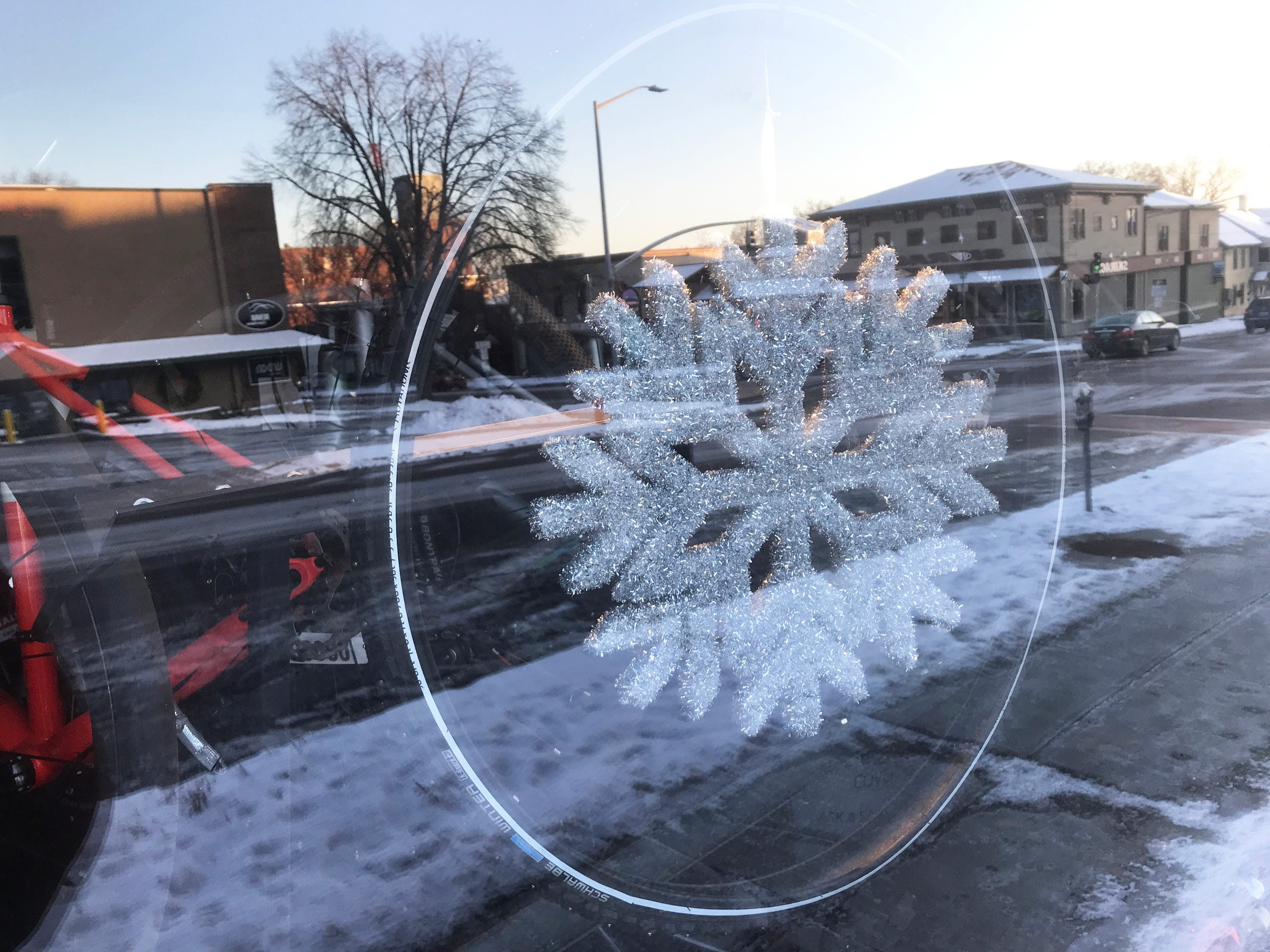 An ornamental snowflake mounted within a bicycle wheel is illuminated by morning sunlight and display-window lights at North Star Sports in Burlington on Dec. 19, 2019.