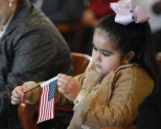 Five-year-old Madalyn Obregon sits with an American flag during the naturalization ceremony, Thursday, Dec. 19, 2019, at the U.S. District Court for the Southern District of Texas. Obregon and her mother came to support a friend getting their citizenship.