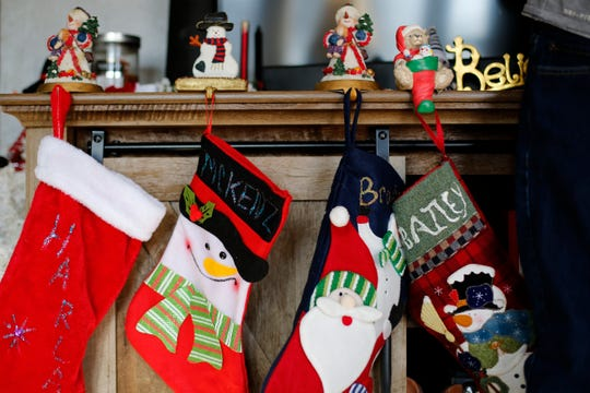 Christmas stockings hang from the mantle in the Allen family home in Colerain, Ohio, on Thursday, Dec. 19, 2019. The Allen family lost its youngest son, Brody, to brain cancer just two weeks before their son Andrew was hit by a car and fell into a coma. Andrew is currently healthy and on the mend preparing to begin a new job.