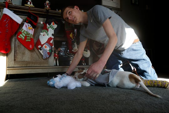 Andrew Allen plays with his new puppy, Harland, at their family's home in Colerain, Ohio, on Thursday, Dec. 19, 2019. Harland was adopted by the Allen family today, after being rescued by SPCA Cincinnati when he was found inside a trash bag on the side of the road. The puppy currently has a cast on his back leg, which will heal, but will later need one of its front legs amputated due to an improperly healed fracture.