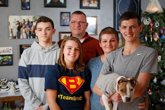 Todd and Shilo Allen post with three of their children Andrew, Alex, and Bailey, along with new puppy, Harland, in the living room of their home in Colerain, Ohio, on Thursday, Dec. 19, 2019.
