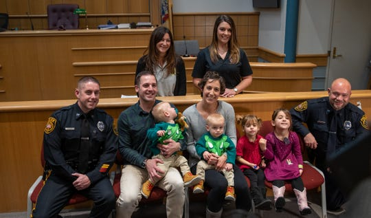 From left to right: (top) Dispatcher Olivia Klein, and Dispatcher Julie Kozo; (bottom) Officer Michael Casey, Robert Glaser and Haley Glaser holding twins Liam and Milo, Livi Glaser, Isla Glaser, and Officer Frank Mahon.