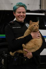 """Norwalk police officer Kirstin Koestler stands with a cat who was rescued by Whiskers TNR of Warren County. The police department is partnering with the organization in a program similar to No Shave November that it calls """"Whiskers for Whiskers."""""""