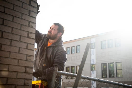 Jaron Rohde works on installing anchor bolts for awnings on the new Cityview townhome development along Keo Way and I-235 on Thursday, Dec. 19, 2019, in Des Moines.