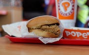 This Aug. 22, 2019, file photo shows a chicken sandwich at a Popeyes restaurant in Kyle, Texas. The chicken sandwich craze, along with and international swine fever outbreak, is expected to boost 2020 poultry demand.